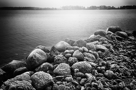 Rocks by water in black and white with film noir feeling Stock Photo