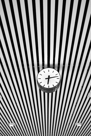Clock with graphic lined ceiling as background