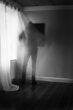 Person in motion blur in front of brightly lit window with curtain, spooky feeling in black and white. Stock Photo