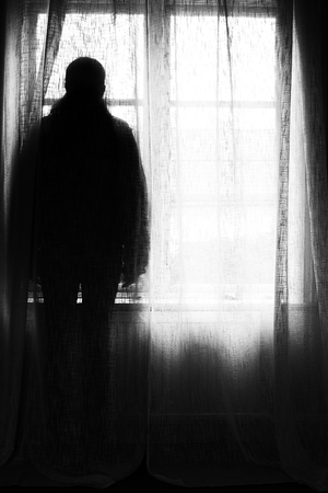Sillhouette of a person standing in front of a window.