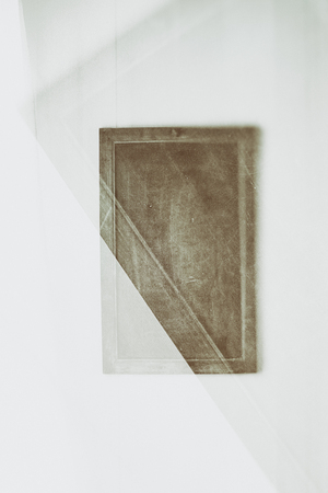 Artistic, creative image of simple board on a wall, partly blurred.