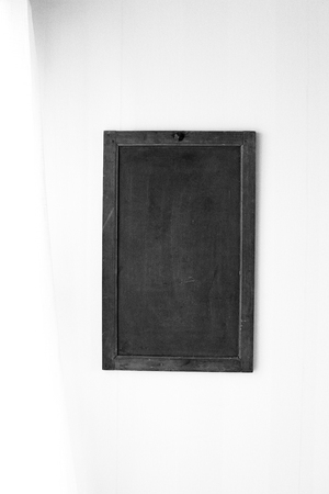Empty blackbord on wall in a brightly lit room, in black and white. Stock Photo