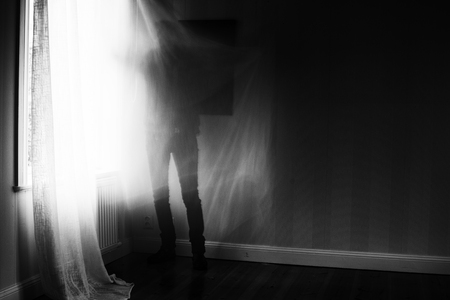 Artistic image with motion blur and grain of person standing in front of window, spooky feeling.