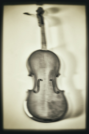Artistic monochrome violin in motion blur with frame