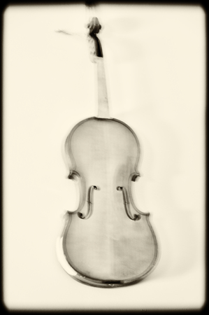 Creative image of violin in motion blur in sepia. Stock Photo