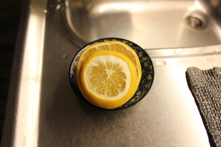Sliced lemon in a bowl on a kitchen sink.