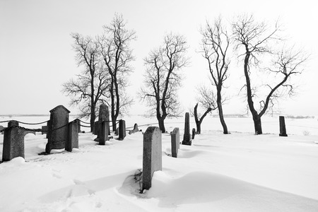 Black and white image of a tranquil winter day at a graveyard. Stock Photo
