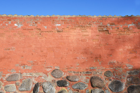 Ancient brick wall with stones and blue sky as background Stock Photo