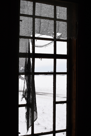 Old window in abandoned house with broken curtains