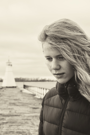 Young girl thinking of a decision. Lighthouse in background.