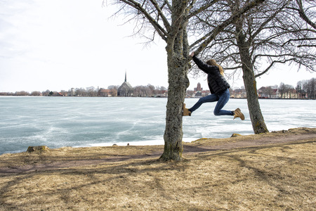 Parkour girl jumping up in tree in park by froxen lake.
