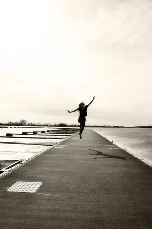Child with energy running and jumping on wooden jetty in the spring