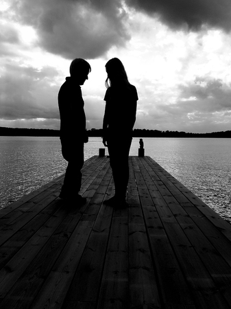 Two unrecognizable people talking on a wooden jetty at sunset