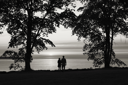 Black and white image of unrecognazible couple standing next to each other by the water.