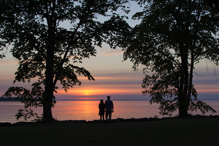 Silhouettes of unrecognizable man and woman watching the sunset. Stock Photo