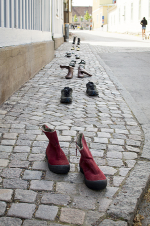Old shoes in a row on sidewalk. Stock Photo