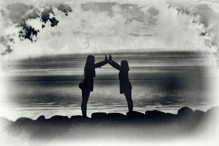 Artistic, crackled, black and white image of silhouettes of two ypung women making a formation with their arms.