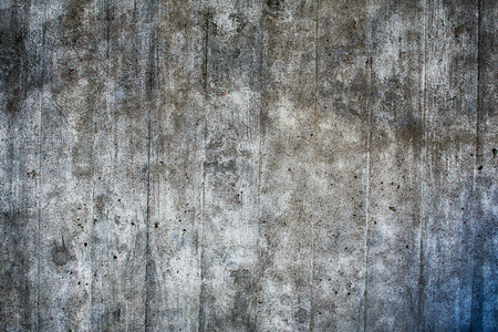 Closeup of rough old concrete wall with cracks and pattern.