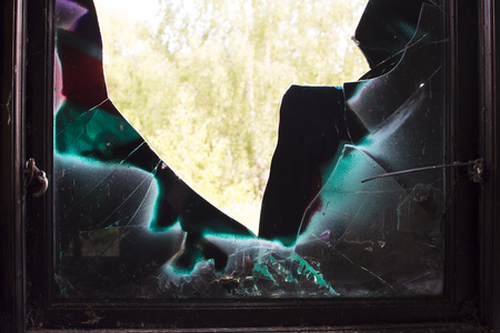 Old window with cracked glass painted in different colors.