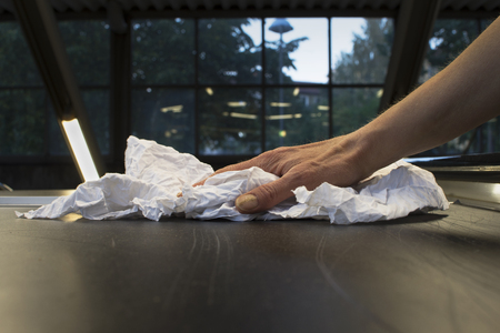 Closeup of hand cleaning a surface with a rag. Stock Photo