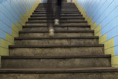 Legs in motion blur running up stairs in subway station.