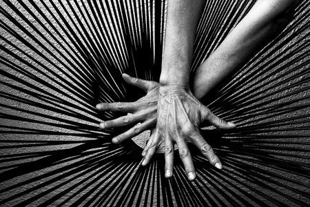 Human hands on black lines pattern in black and white. Stock Photo