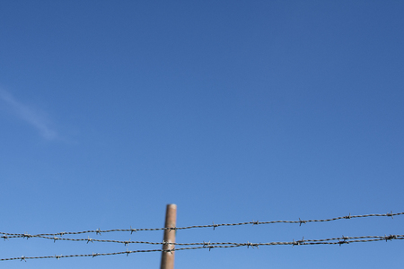 Closup of barbed wire with industrial chimney in the background against blue sky