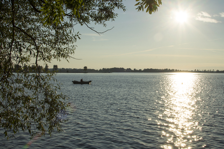 A silhouette of a fisherman in a boat at a big lake with the sun glistening in the water.