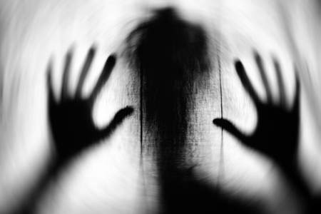 Textured image in motion blur of scary ghost as a silhouette with big hands. Stock Photo
