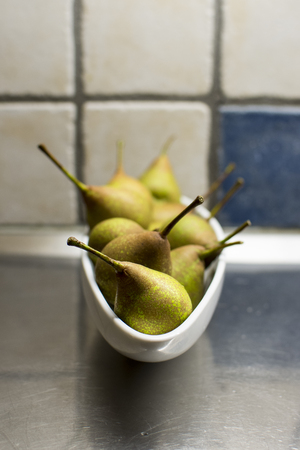 Closeup of fresh pears in an oval white bowl in the kitchen, short depth of field.