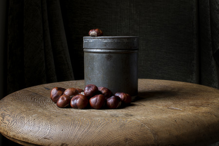Autumn still life with an old tin canister and chestnuts vintage style.