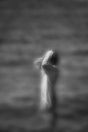 Surreal blurred black and white image of unrecognizable woman standing in water.