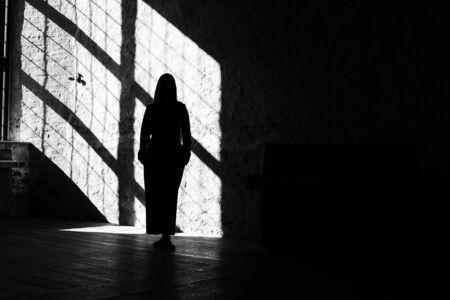 Silhouette einer Yong-Frau mit Licht aus einem alten Fenster, gruseliges Gefühl.