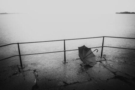Black and white image of forgotten umbrella a rainy day by the water. 写真素材