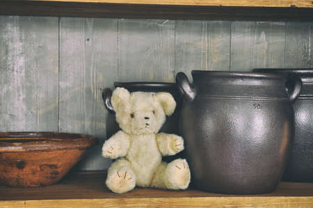 Closeup of vintage cabinet with an old teddybear sitting on a shelf with ceramic pots and bowl. Retro style