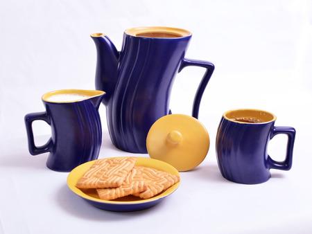 utensilios de cocina: café azul y amarillo con una jarra de leche y galletas en un plato sobre un fondo blanco.