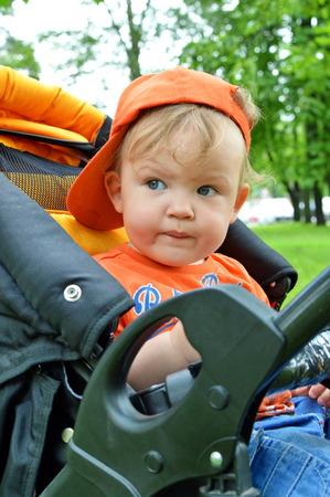 the little boy in the orange hat in stroller
