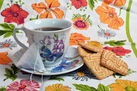 Cup with tea and biscuits on colorful tablecloths. Stock Photo