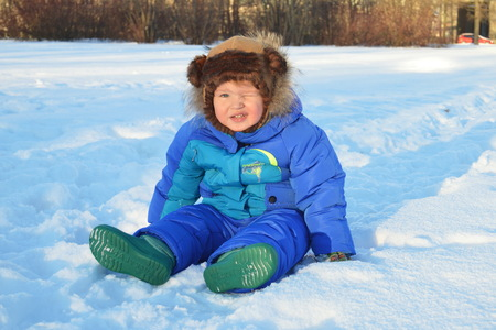 A little boy is sitting on the white snow.