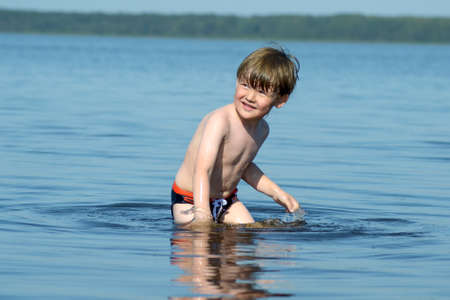 A little boy swims in the lake in the summer