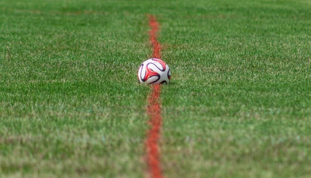 Red and White Soccer Ball at Midfield
