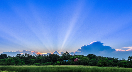 Big Sky with Streaking Rays of Sun Over Red Barn