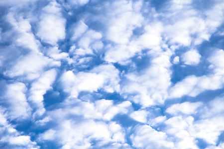 Fluffy white clouds against a blue sky background.