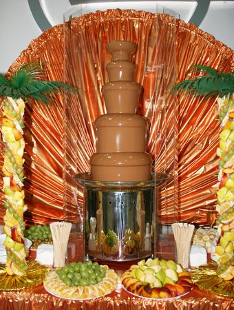 Chocolate fondue fountain with marshmallow being dipped