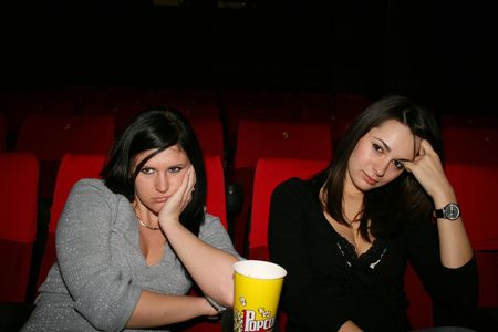 girls are in the cinema, look the boring film