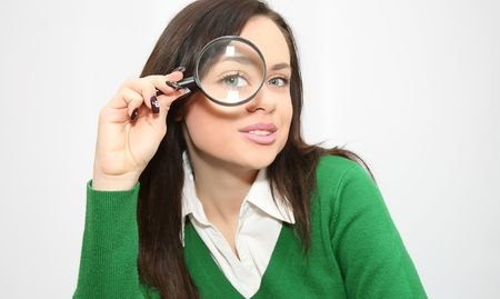 student holds magnifying glass up to the eye for fun, and funny photo