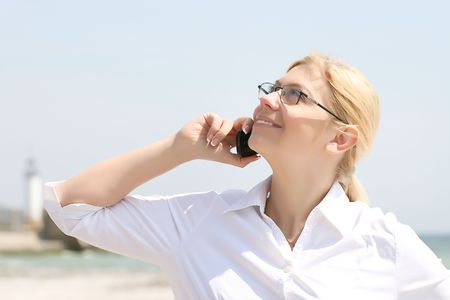 business woman talks by phone on a beach