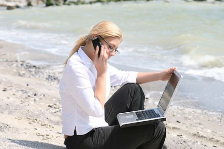 Businesswoman with business suit working on the beach photo