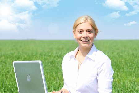 Business lady typing on laptop, sitting outdoors.