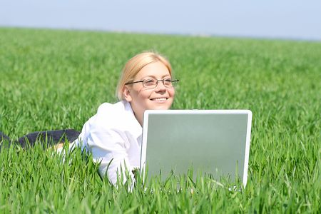 Portrait of businesswoman lying on green grass with laptop near Stock Photo